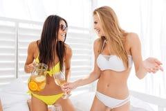 Deux jeunes filles sexy de sourire ayant l'amusement et buvant de la limonade Photo libre de droits