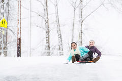 Deux jeunes filles sledding en bas de la colline dans la glace et la neige Image stock