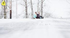 Deux jeunes filles sledding en bas de la colline dans la glace et la neige Image libre de droits