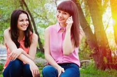 Deux jeunes filles souriant avec le téléphone portable Photographie stock libre de droits