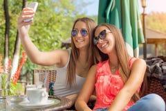 Deux jeunes filles souriant et prenant le selfie Image libre de droits
