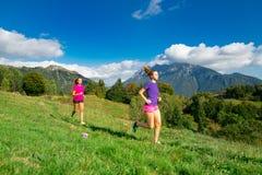 Deux jeunes filles sportives courant ensemble sur l'herbe dans un mounta Photo stock
