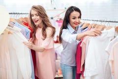 Deux jeunes filles sur des achats Les filles choisissent des vêtements dans le magasin Filles dans la salle d'exposition Photo stock