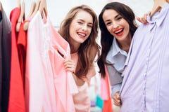 Deux jeunes filles sur des achats Les filles choisissent des vêtements dans le magasin Filles dans la salle d'exposition Images libres de droits