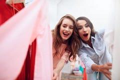 Deux jeunes filles sur des achats Les filles choisissent des vêtements dans le magasin Filles dans la salle d'exposition Photographie stock