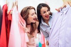 Deux jeunes filles sur des achats Les filles choisissent des vêtements dans le magasin Filles dans la salle d'exposition Photos stock