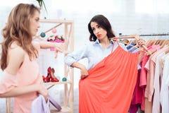 Deux jeunes filles sur des achats Les filles choisissent des vêtements dans le magasin Filles dans la salle d'exposition Photo libre de droits