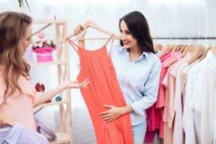 Deux jeunes filles sur des achats Les filles choisissent des vêtements dans le magasin Filles dans la salle d'exposition Photos libres de droits