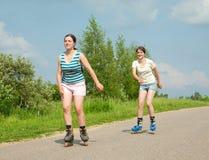 Deux jeunes filles sur des lames de rouleau photo libre de droits