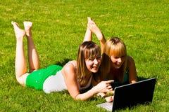 Deux jeunes filles sur l'herbe avec le cahier Photographie stock