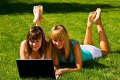 Deux jeunes filles sur l'herbe avec le cahier Image stock