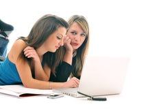 Deux jeunes filles travaillent sur l'ordinateur portatif d'isolement Photo libre de droits