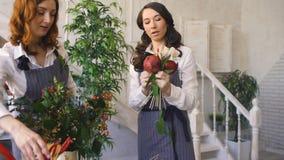 Deux jeunes fleuristes beaux de chef travaillent aux fleurs portent des fruits boutique faisant le bouquet de fruits et légumes banque de vidéos