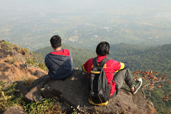 Deux jeunes garçons avec le sac à dos prenant se reposer sur le dessus d'une montagne et apprécier la vue de vallée Images stock