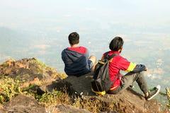 Deux jeunes garçons avec le sac à dos prenant se reposer sur le dessus d'une montagne et apprécier la vue de vallée Photos libres de droits