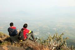 Deux jeunes garçons avec le sac à dos prenant se reposer sur le dessus d'une montagne et apprécier la vue de vallée Images libres de droits