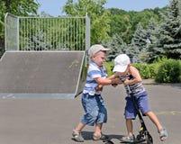 Deux jeunes garçons combattant au-dessus d'un scooter Photographie stock libre de droits