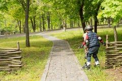 Deux jeunes garçons dans des lames de rouleau Photographie stock libre de droits