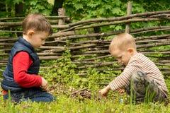 Deux jeunes garçons jouant à allumer un feu de camp Images stock