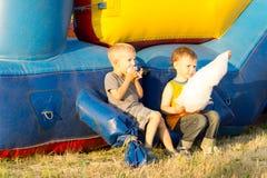 Deux jeunes garçons mangeant la coton-sucrerie près d'une glissière Image stock