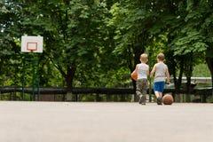 Deux jeunes garçons marchant outre d'un terrain de basket Image stock