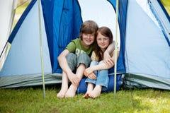 Deux jeunes garçons reposant en Front Of une tente Photos stock