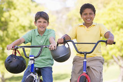 Deux jeunes garçons sur des bicyclettes souriant à l'extérieur Image libre de droits