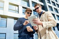 Deux jeunes hommes à l'aide de la Tablette au soleil Photographie stock libre de droits