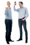 Deux jeunes hommes à l'aide de leur téléphone Photo stock