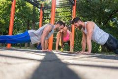 Deux jeunes hommes battant des mains de la position de planche pendant la séance d'entraînement d'associé Image libre de droits