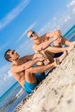 Deux jeunes hommes beaux causant sur une plage Photo libre de droits