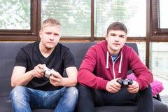 Deux jeunes hommes beaux jouant des jeux vidéo tout en se reposant sur le sofa Photo stock