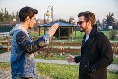 Deux jeunes hommes beaux saluant en parc Image libre de droits