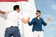 Deux jeunes hommes beaux saluant la position sur le yacht Photos libres de droits