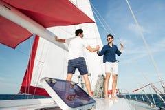 Deux jeunes hommes beaux saluant la position sur le yacht Photo libre de droits