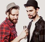 Deux jeunes hommes chantant avec le microphone D'isolement sur le fond blanc Photo stock