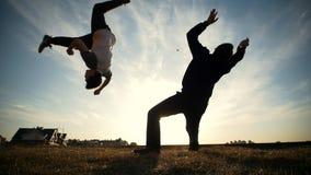 Deux jeunes hommes combattant dehors sur le coucher du soleil banque de vidéos