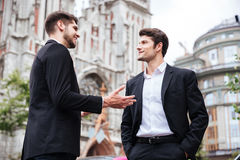 Deux jeunes hommes d'affaires gais se tenant et parlant Photos libres de droits