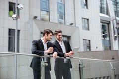 Deux jeunes hommes d'affaires heureux discutant le projet et à l'aide du comprimé Photos libres de droits