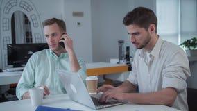Deux jeunes hommes d'affaires professionnels travaillent dans une lumière et un bureau ouvert moderne de plan images stock