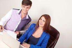 Deux jeunes hommes d'affaires réussis de sourire heureux travaillant avec le document ou le contrat au bureau Images stock