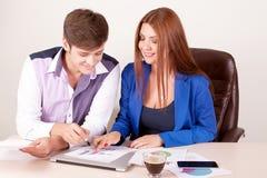 Deux jeunes hommes d'affaires réussis de sourire heureux travaillant avec le document ou le contrat au bureau Photo stock