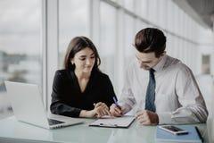 Deux jeunes hommes d'affaires réussis de sourire heureux travaillant avec le document ou le contrat au bureau Succès dans les aff Images stock