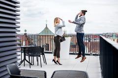 Deux jeunes hommes d'affaires se tenant sur une terrasse en dehors du bureau, exprimant l'excitation photo libre de droits