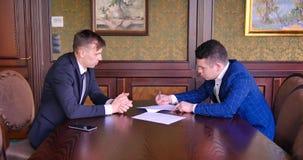 Deux jeunes hommes d'affaires signent un contrat L'associé, investisseur, affaire, négocient, discutent, cryptocurrency, bureau banque de vidéos