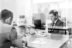 Deux jeunes hommes d'affaires utilisant l'ordinateur portable lors de la réunion d'affaires Photographie stock