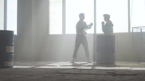 Deux jeunes hommes dans des vêtements sport dans la danse de pratique abandonnée poussiéreuse foncée de bâtiment devant la fenêtr banque de vidéos