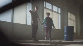 Deux jeunes hommes dansant dans la salle sombre et poussi?reuse du b?timent abandonn? Adolescents entreprenant la d?marche de dan banque de vidéos