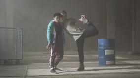 Deux jeunes hommes dansant dans la salle sombre et poussi?reuse du b?timent abandonn? Les types entreprenant des démarches et des banque de vidéos