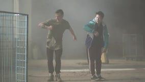 Deux jeunes hommes dansant dans la salle sombre et poussi?reuse du b?timent abandonn? Les types entreprenant des d?marches et des banque de vidéos